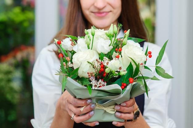 O proprietário de uma loja de flores faz um buquê com rosas brancas
