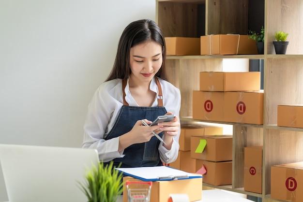 O proprietário de uma pequena empresa vestindo um avental tem sucesso nas vendas on-line usando uma caixa de pacote para smartphone colocada em casa.