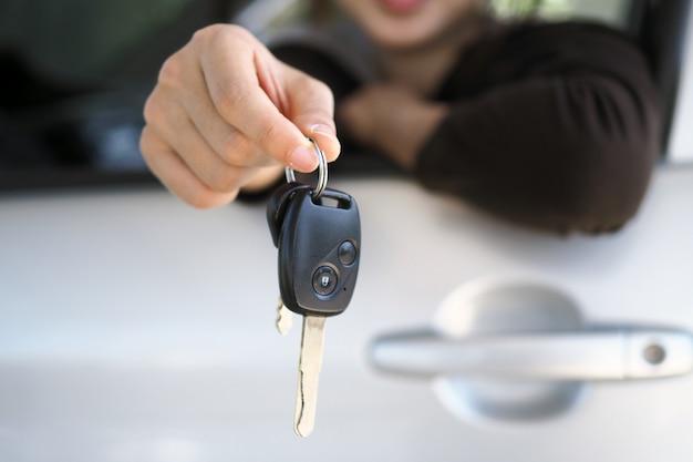 O proprietário do carro está de pé as chaves do carro para o comprador