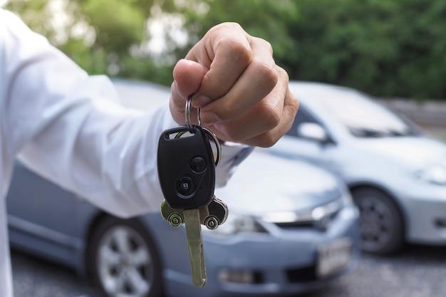 O proprietário do carro está de pé com as chaves do carro para o comprador. vendas de carros usados