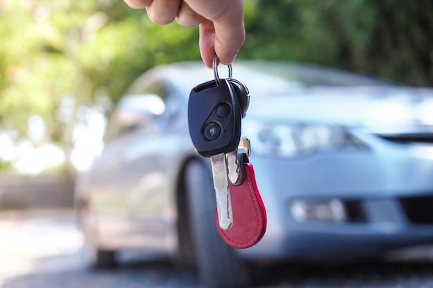 O proprietário do carro está de pé com as chaves do carro para o comprador