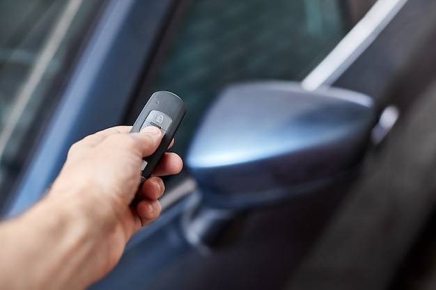 O proprietário do carro tem na mão um dispositivo de controle remoto para entrada sem chave