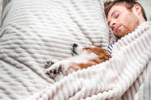 O proprietário dorme com seu cachorro na cama, debaixo de um cobertor. fundo branco. fim de semana de conceito. conceito de sono e descanso. copie o espaço