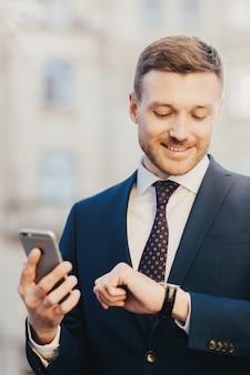 O proprietário não barbeado satisfeito da corporação masculina olha feliz no relógio de pulso