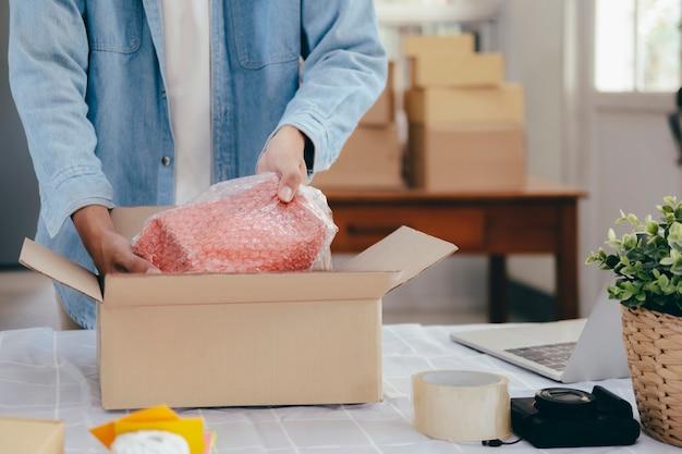 O proprietário pequeno da empresa em linha prepara o produto envia ao cliente