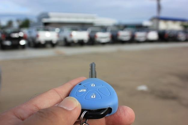 O proprietário usando a chave do controle remoto procurando em seu carro no estacionamento