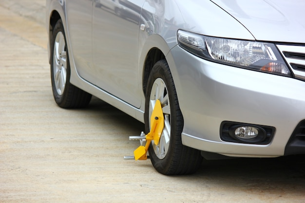 O proprietário usou a roda travada em seu carro de passageiros cinza anti-roubo