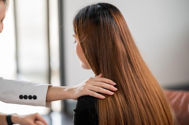 O psicólogo toca no ombro e presta assistência na compreensão dos problemas de uma paciente