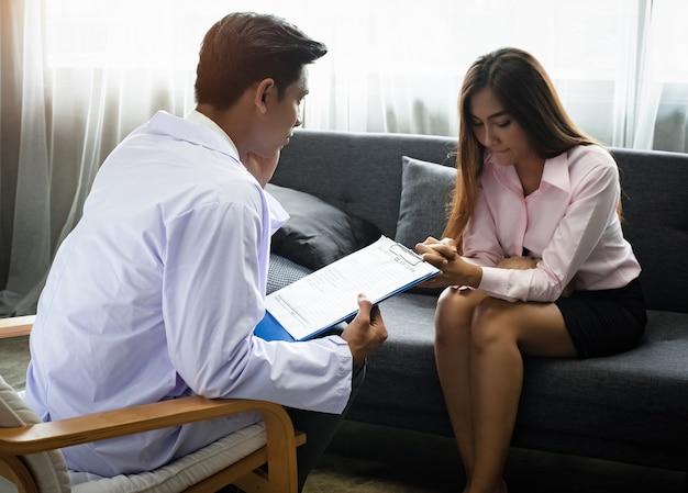 O psiquiatra está conduzindo uma consulta para a mulher do estresse, luz embaçada ao redor