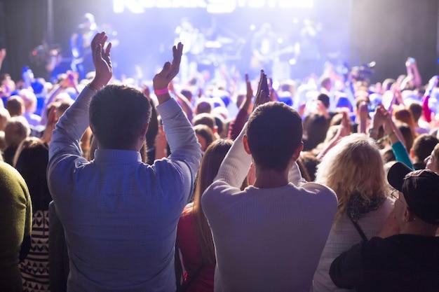 O público assistindo ao show no palco do grande clube de concertos.