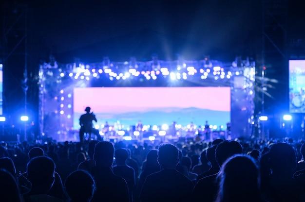 O público jovem de silhueta está assistindo o concerto noturno