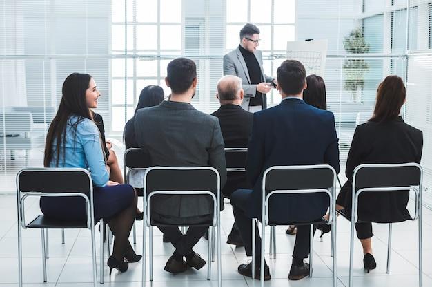 O público ouve o palestrante na sala de conferências