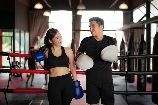 O pugilista asiático ostenta a menina e o instrutor que olham o sorriso quando inclinado em cordas vermelhas pretas no anel de boxe