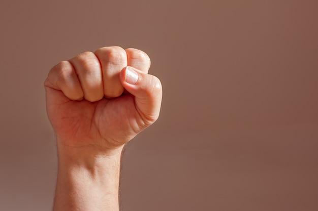 O punho cerrado de um homem branco erguido. conceito de resistência, solidariedade e desafio.