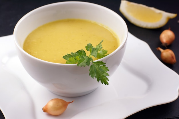 O purê de sopa amarelo é servido em um prato branco em um restaurante.