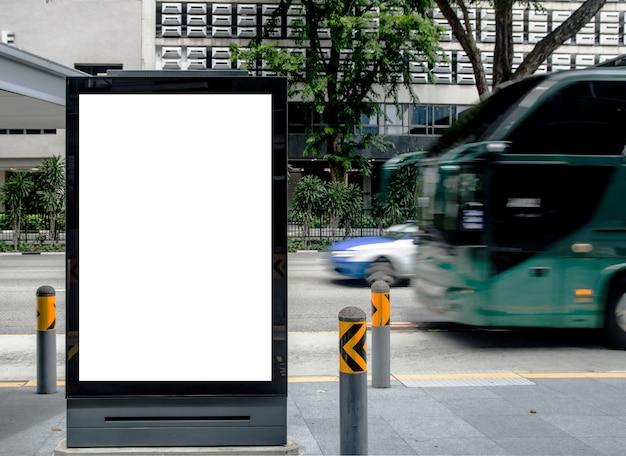 O quadro de avisos vazio vertical na parada do ônibus exterior anuncia na zombaria da rua acima.