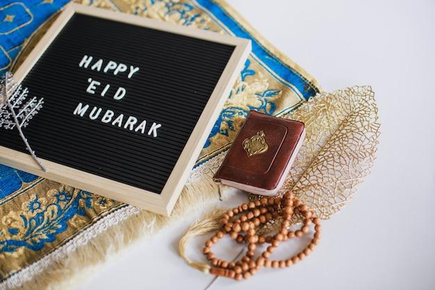 O quadro diz: feliz eid mubarak no tapete de oração com o livro sagrado al quran e contas de oração. há uma letra árabe que significa o livro sagrado