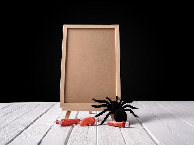 O quadro-negro no stand com halloween black aranha e dedo no assoalho de madeira black b