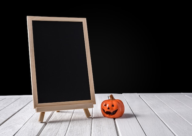 O quadro-negro no stand com halloween pumpkins no piso de madeira e fundo preto