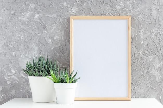 O quadro vazio branco vertical de madeira e duas plantas suculentas naturais florescem em vasos brancos.