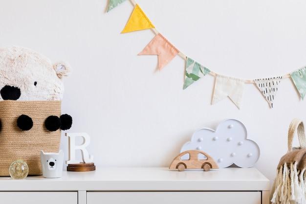 O quarto do bebê recém-nascido escandinavo moderno com espaço de cópia, carro de madeira, brinquedos de pelúcia e nuvens. bandeiras de algodão penduradas e estrelas brancas. interior minimalista e aconchegante com paredes brancas.