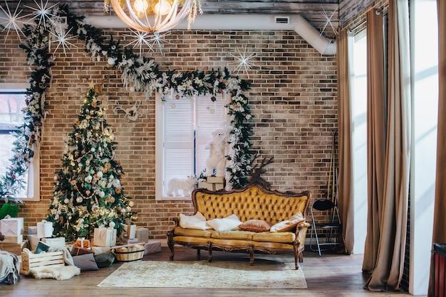 O quarto em estilo loft é decorado com decorações de ano novo. sofá de couro vintage luxuoso e árvore de natal.