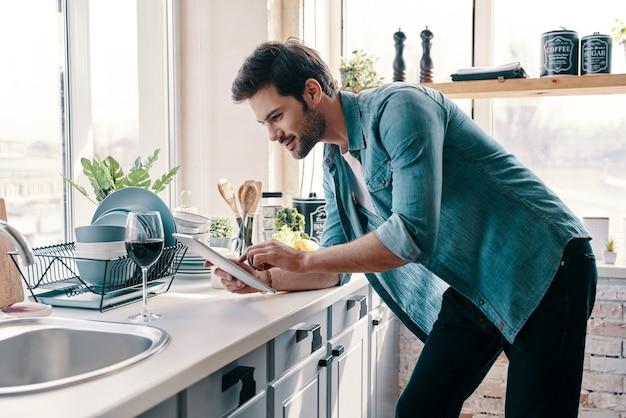 O que cozinhar? jovem bonito no casual wear usando tablet digital e sorrindo enquanto está na cozinha em casa