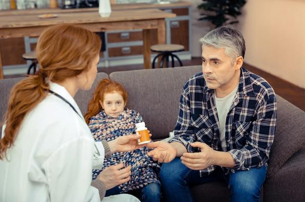O que devo fazer. homem simpático e triste a fazer perguntas ao médico enquanto se preocupa com a filha