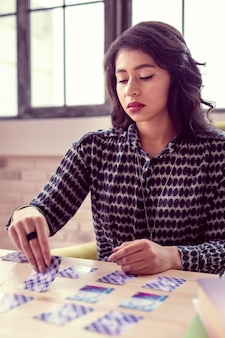 O que dizem os cartões. mulher séria e bonita pegando uma carta de tarô enquanto se concentra no trabalho