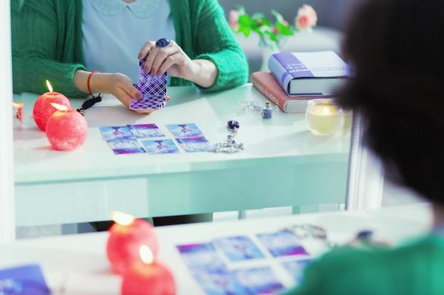 O que dizem os cartões. reflexo no espelho das cartas de tarô em mãos femininas enquanto são usadas para contar o futuro