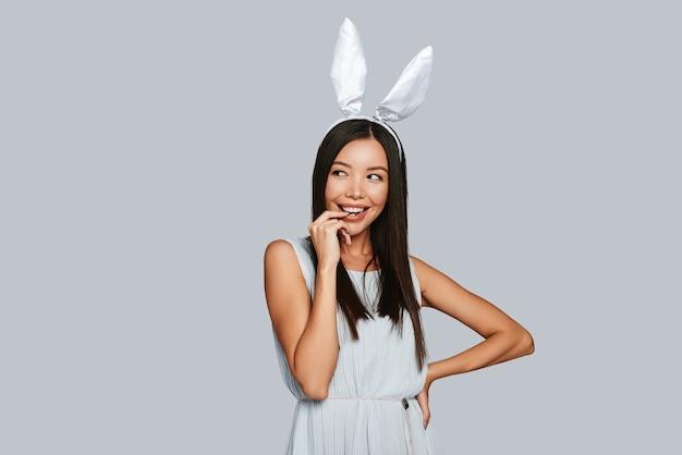 O que é aquilo? curiosidades, jovem asiática com orelhas de coelho, sorrindo em pé contra um fundo cinza