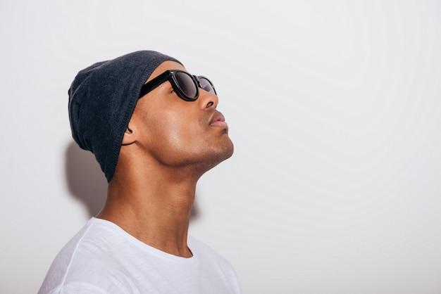 O que é aquilo? vista lateral de um jovem africano bonito em chapéus, olhando para cima