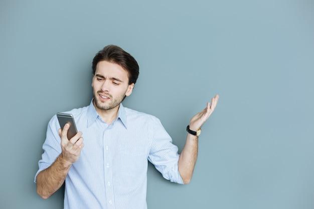 O que é isso. homem agradável e confuso segurando seu smartphone e olhando para a tela