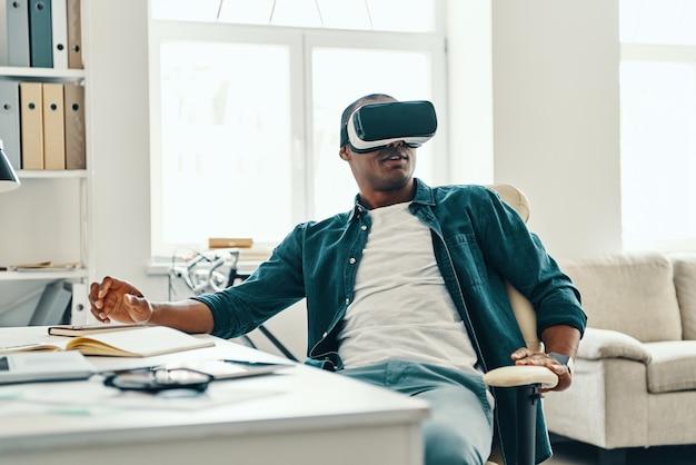 O que é real? jovem africano bonito usando fone de ouvido simulador de realidade virtual enquanto está sentado em casa