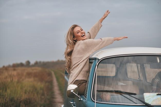O que é vida sem aventuras? mulher jovem e atraente inclinando-se para fora da janela da van e sorrindo enquanto aprecia a viagem de carro com o namorado