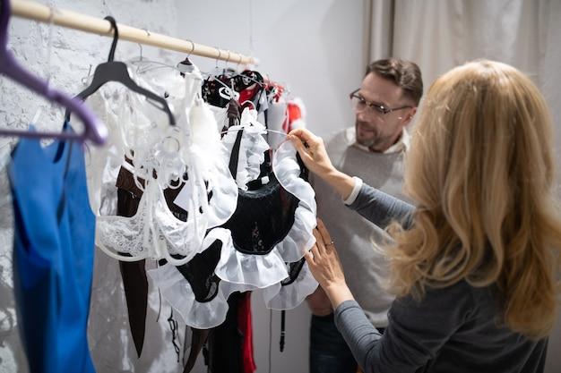 O que escolher. casal feliz olhando através de uma ampla seleção de artigos em uma loja de lingerie.