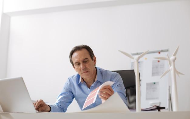 O que escolher. engenheiro profissional sentado no escritório trabalhando no laptop enquanto elabora o projeto de turbinas ecológicas