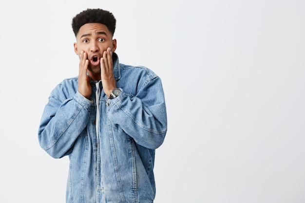O que está acontecendo. close-up de jovem bonito homem de pele escura com penteado afro em jaqueta jeans casual, tocar o rosto com as mãos, olhando na câmera com expressão chocada