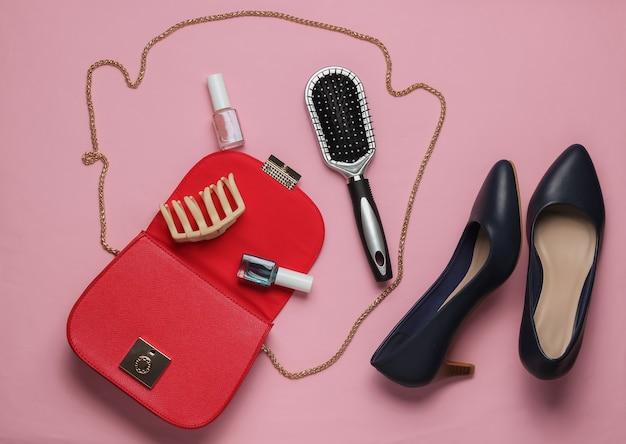 O que está na bolsa feminina bolsa de couro vermelha com acessórios femininos, cosméticos, sapatos de salto alto em fundo rosa