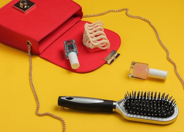 O que está na bolsa feminina bolsa de couro vermelha com acessórios femininos, produtos cosméticos em fundo amarelo