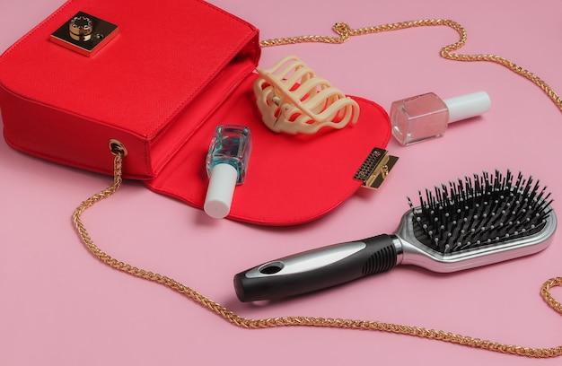 O que está na bolsa feminina bolsa de couro vermelha com acessórios femininos, produtos cosméticos em fundo rosa