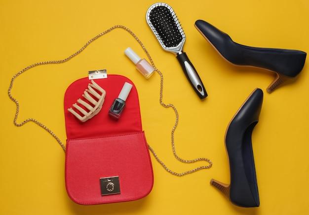 O que está na bolsa feminina bolsa de couro vermelha com acessórios femininos, produtos cosméticos, sapatos de salto alto em fundo amarelo