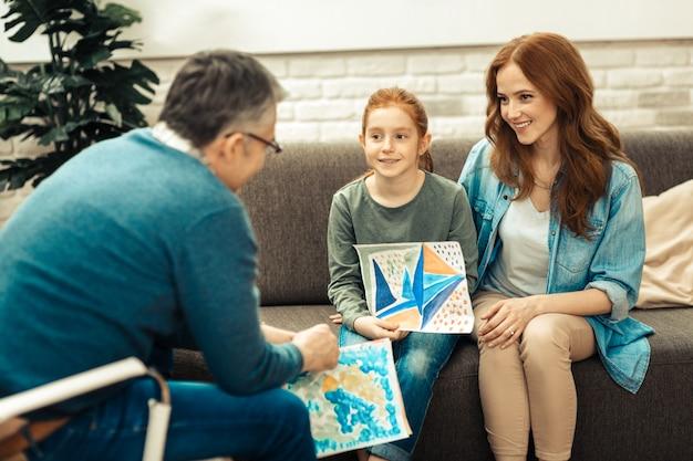 O que eu tenho. menina positiva encantada sorrindo enquanto mostra uma pintura para o médico