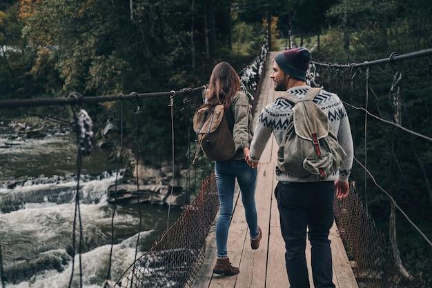 O que há do outro lado? vista traseira de um jovem casal de mãos dadas enquanto caminha na ponte pênsil