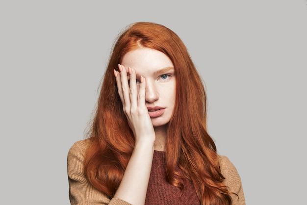 O que há retrato de uma jovem e bonita adolescente com cabelos ruivos sedosos, cobrindo o rosto com a mão e olhando para a câmera em pé contra um fundo cinza