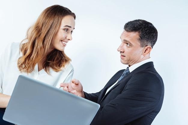 O que você acha. empresários de mente positiva olhando uns para os outros enquanto discutem seu projeto e usam um laptop juntos.
