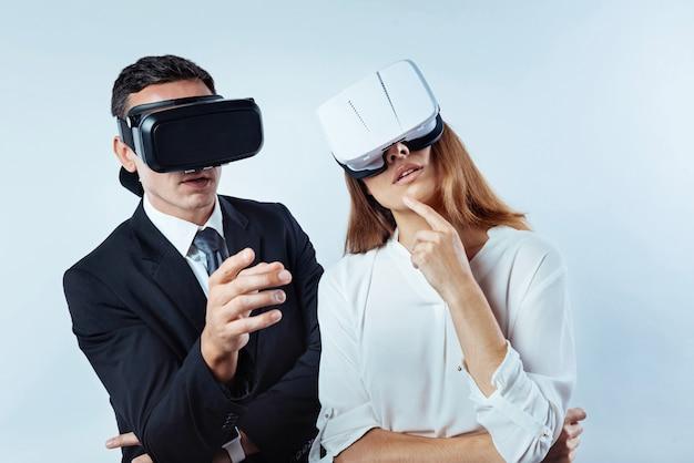 O que você acha. empresários pensativos, próximos uns dos outros, discutindo algo, ambos usando óculos de realidade virtual.