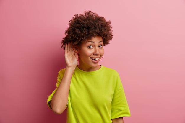 O que você diz? mulher de etnia positiva mantém a mão perto do ouvido para ouvir melhor, bisbilhotando informações privadas, usa uma camiseta casual, posa contra uma parede rosa, ouve algo interessante