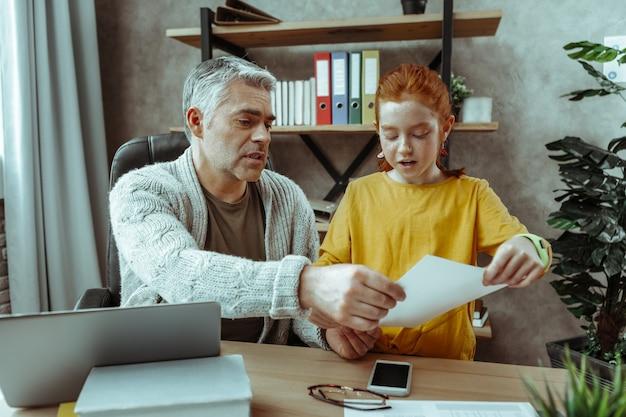 O que você está fazendo. garota simpática e agradável em pé perto do pai enquanto lia o documento