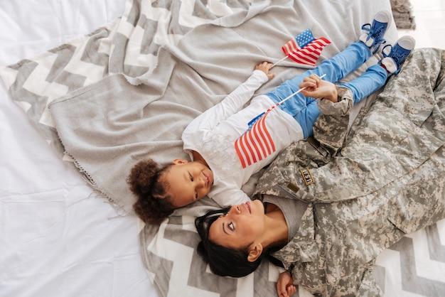 O que você pensa sobre. maravilhosa mãe feliz e amorosa e sua filha deitada em um cobertor pensando nas férias juntas, enquanto ainda seguram bandeirinhas nas mãos